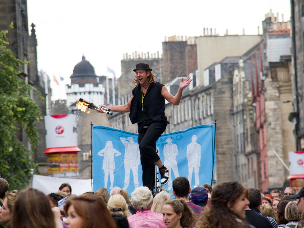 Man juggling fire in front of crowd at Edinburgh Fringe festival.