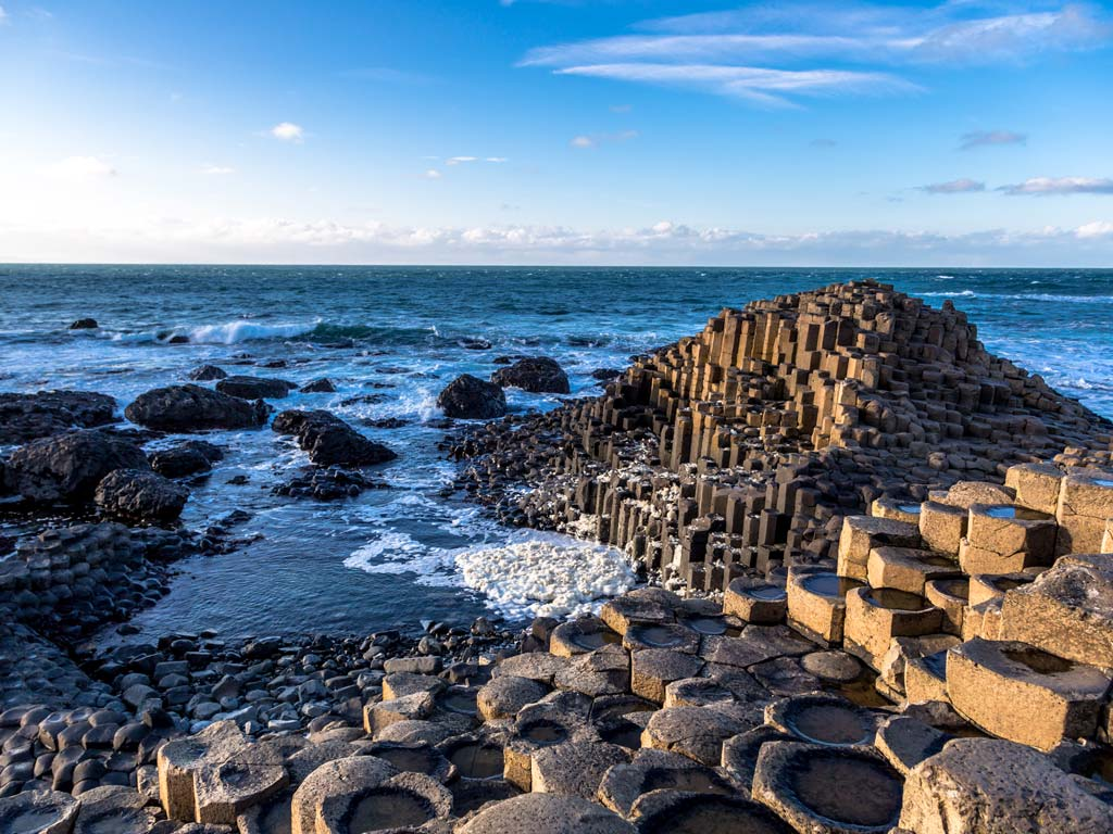Basalt columns of Ireland's Giant's Causeway sticking out into the ocean.