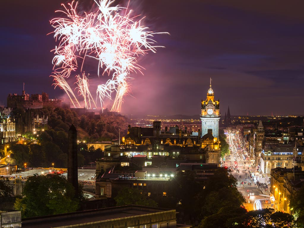 Aerial view of fireworks going off above Edinburgh city center.