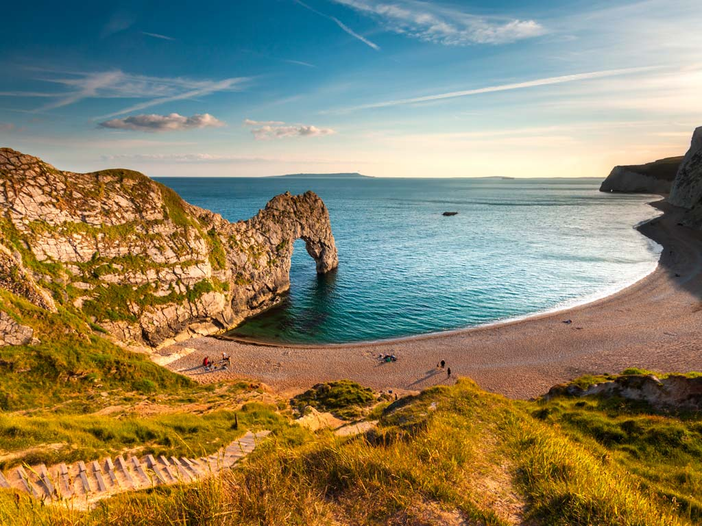 Sunset view of Dorset coast with Durdle Door rock formation.