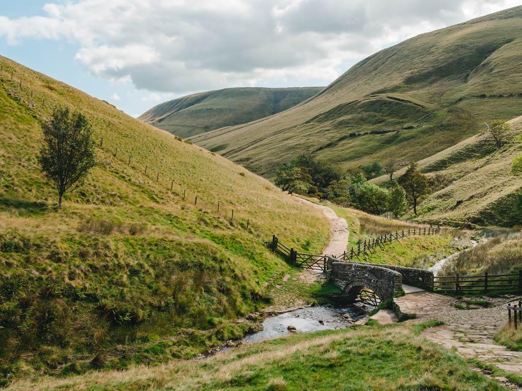Rolling green hills of UK Peak District with stone bridge crossing small stream.