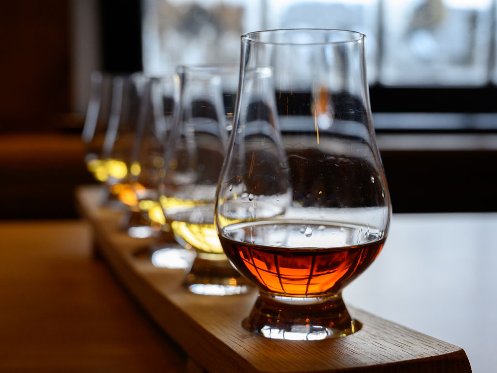 Row of Scotch snifter glasses partially filled.