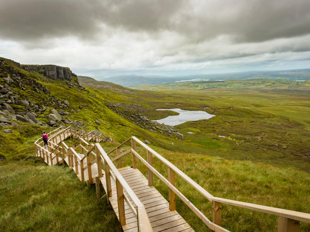 View of wooden path and green hills of Ireland's Stairway to Heaven.