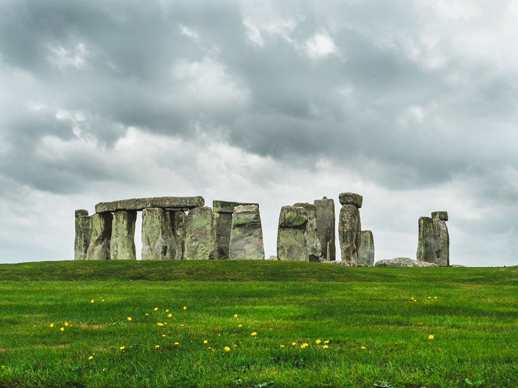 Stonehenge circle with grassy hill in foreground.