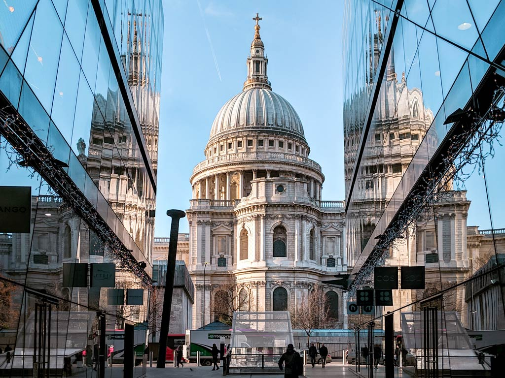 View of St. Paul's Cathedral from alleyway lined with glass buildings.