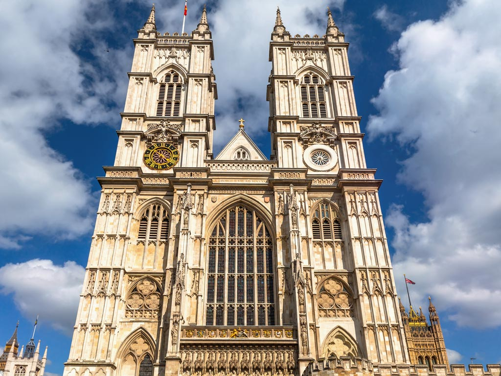 Front exterior of Westminster Abbey with two towers and stained glass windows.