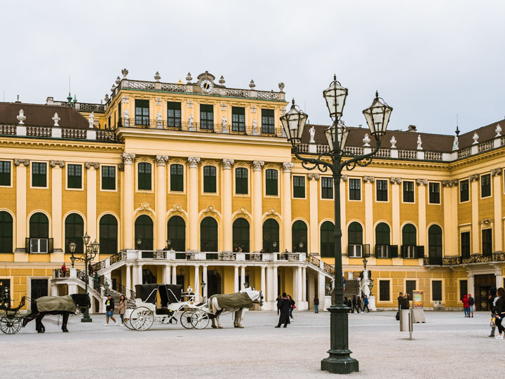 Yellow facade of Schonbrunn Palace with horse carriages and lamp post