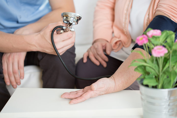 VisitHealth Review - Nurse taking woman's blood pressure in living room