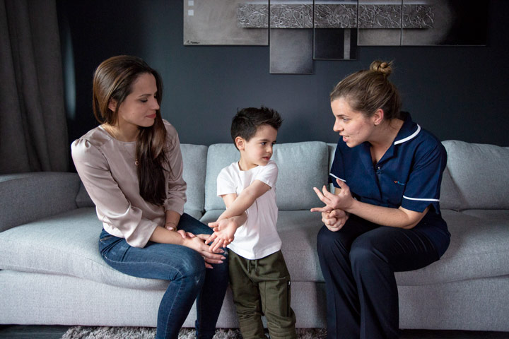 Nurse talking to child and mother on sofa