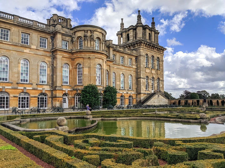 Garden hedge and pool in front of Blenheim Palace exterior