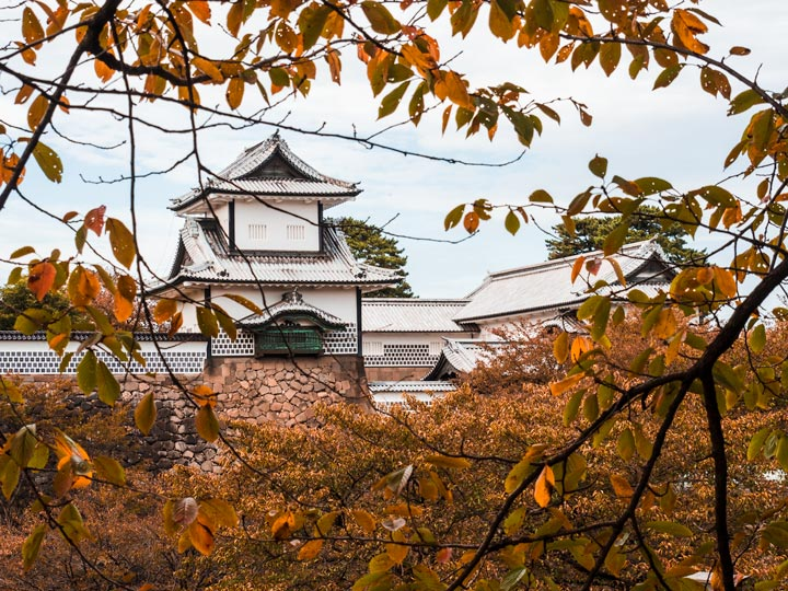 Kanazawa castle viewed through orange autumn leaves