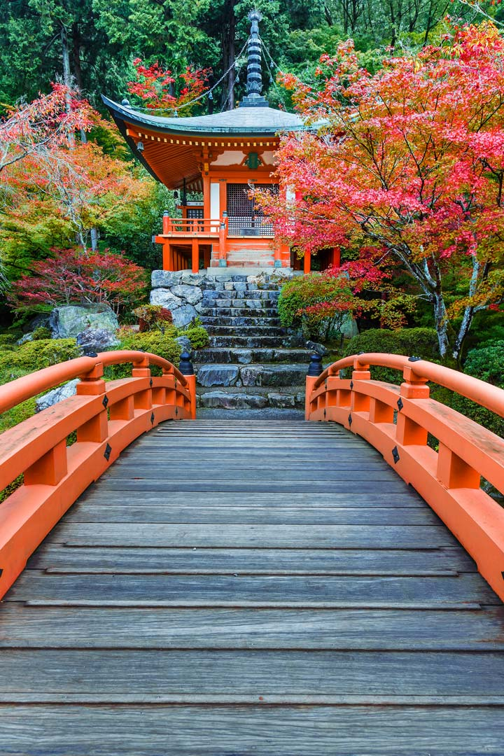 Traditional Japanese temple with orange wooden bridge leading to it