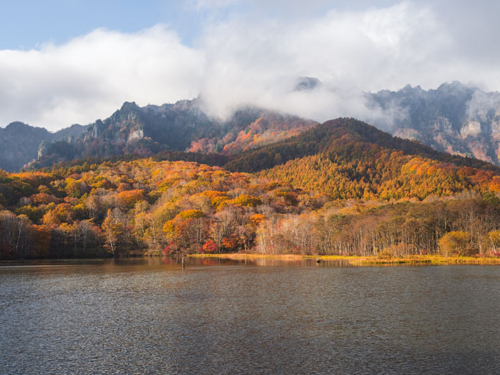 Togakushi Mirror Lake with fall foliage and white clouds