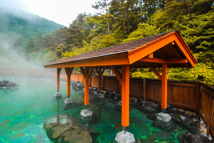 Japanese hot spring in forest with pavilion