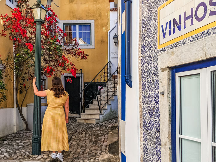 Girl in yellow dress in Cascais alley with flowers