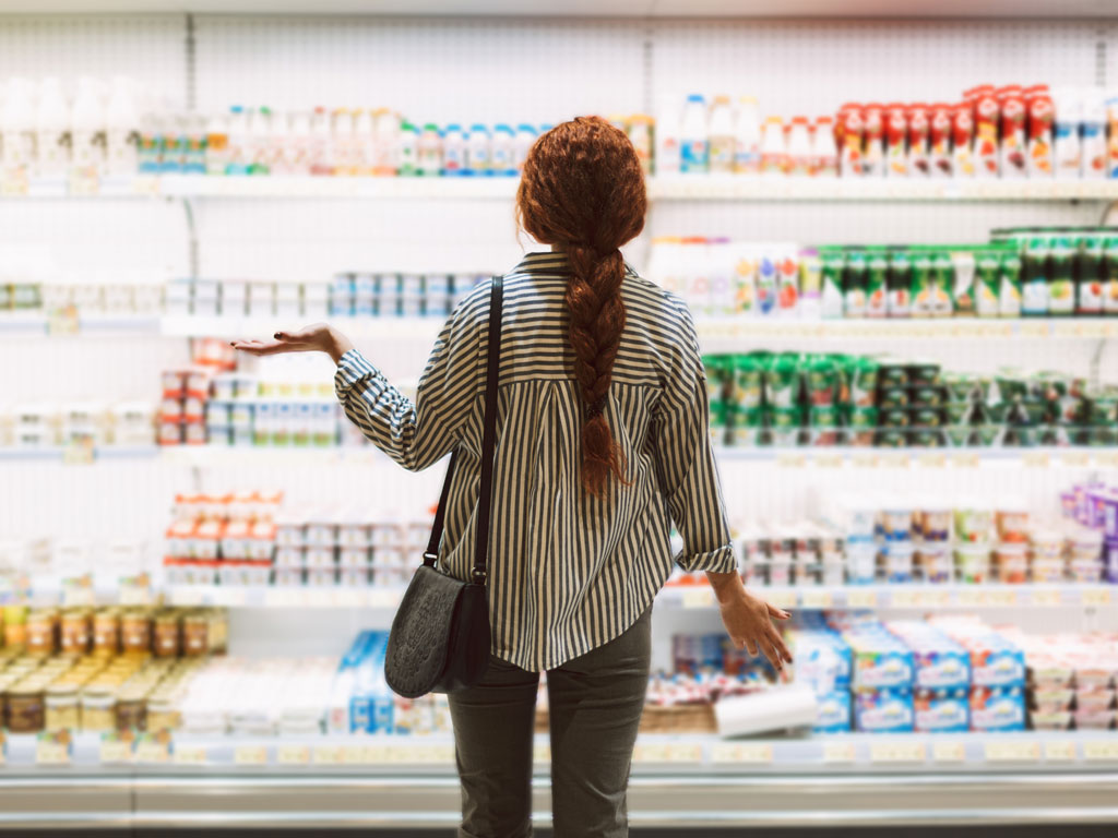 Young woman standing in front of dairy aisle wondering where to buy American food in the UK.