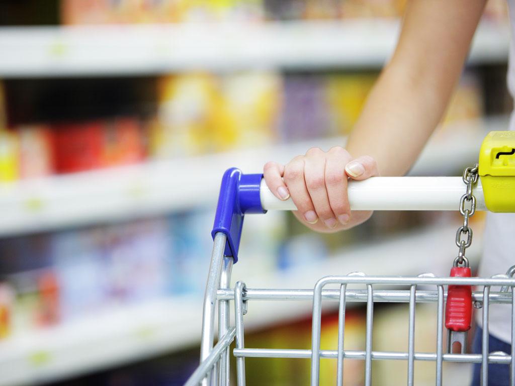 Woman pushing shopping cart down UK American food shop aisle.